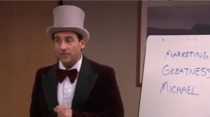 Michael Scott dressed as Willy Wonka, presenting his Golden Ticket idea